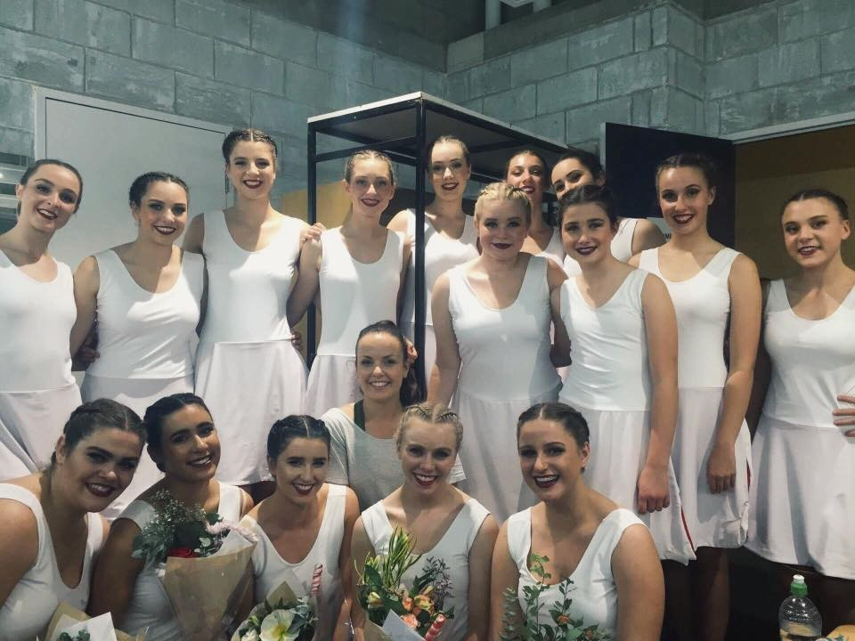 Dance troupe back stage in their wonderful white dresses with the girls in the front row holding bouquets of flowers after the show.